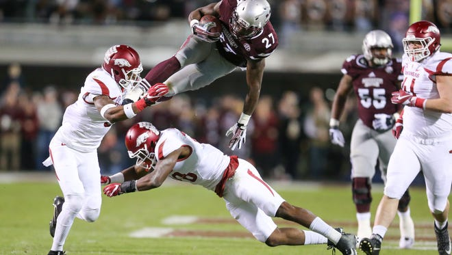 Mississippi State's Aeris Williams (27) leps over an Arkansas defender in the first quarter. Mississippi State played Arkansas in an SEC football game on Saturday, November 19, 2016 at Davis Wade Stadium in Starkville, MS. Photo by Keith Warren/For The Clarion-Ledger