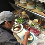 Chef Jaime Mateo assembles two breakfast dishes at Mermaid Garden Cafe.