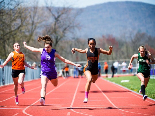 Central York's Haven Evans crosses the finish line in front of Northern's Jordan Clark in the girls' 100-meter dash Saturday at Northern High School in the Arctic Blast Track and Field Invitational.