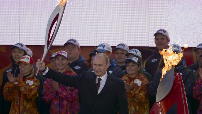 Lighting the Olympic flame in Moscow last October, Russian President Vladimir Putin starts the torch relay to Sochi.
