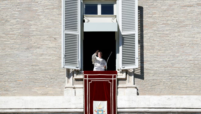 Pope Francis delivers his blessing during the Angelus noon prayer he celebrated from the window of his studio overlooking St. Peter's Square, at the Vatican Oct. 30, 2016.