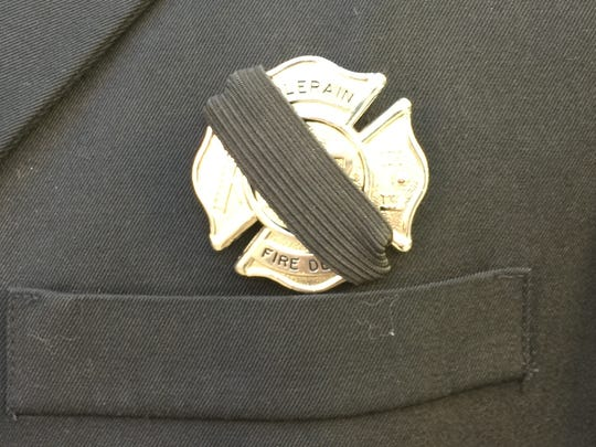 Many firefighters to attend FAO Daryl Gordon's Tuesday viewing wrapped black bands around their badges. Badges adorning some passing emergency vehicles were also covered with black strips.