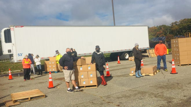 Massachusetts Military Support Foundation volunteers distribute boxes of food Saturday morning at Cape Cod Community College. In two hours, they stocked 700 cars.