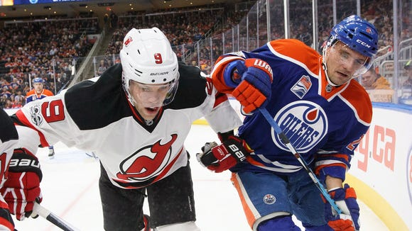 New Jersey Devils' Taylor Hall (9) and Edmonton Oilers' Andrej Sekera (2) battle in the corner during the Thursday's game.