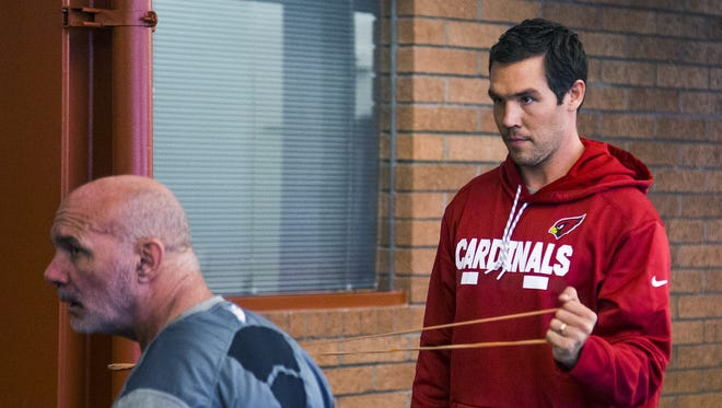 Arizona Cardinals quarterback Sam Bradford stretches as strength and conditioning coach Buddy Morris, left, supervises work outs at the Tempe training facility, Tuesday, April 3, 2018, during the offseason strength and conditioning program.