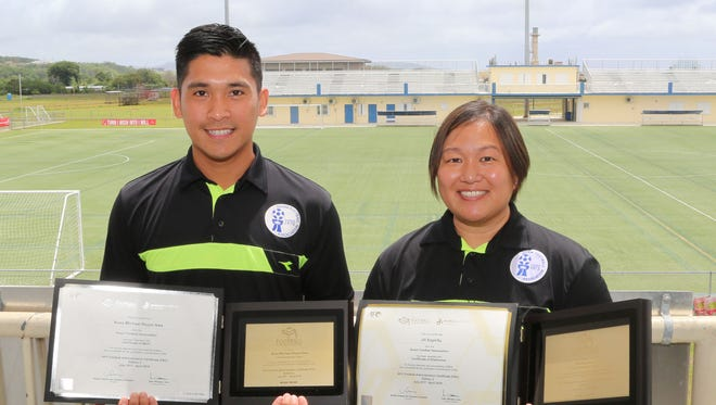 Guam Football Association's Ross Awa, left, and Jill Espiritu, right, pose for a photo at the GFA National Training Center with their graduation certificates from the recently concluded AFC Football Administration Certificate Course. Awa, GFA Goalkeeper Coach Development Officer, graduated Apr. 4 with a Certificate of Merit, the second-highest honor attainable by course participants. Espiritu, GFA Media & Marketing Officer, graduated Mar. 30 with a Certificate of Distinction, the highest honor achievable by participants in the course. Espiritu is one of only four in Asia to earn the Certificate of Distinction.