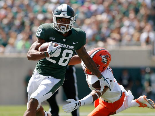 Michigan State running back Madre London gets past Bowling Green's Armani Posey for a first down in the second quarter Saturday, Sept. 2, 2017, in East Lansing.