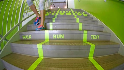 A Utah Valley University student walks down the bright green lanes painted on the stairs from the gym Thursday, June 18, 2015, at Utah Valley University, in Orem, Utah. Utah Valley University spokeswoman Melinda Colton said  the green lanes were intended as a lighthearted way to brighten up the space and get students' attention.