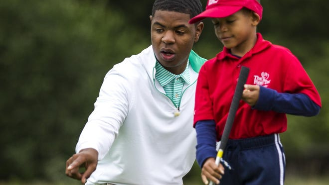 Earl Cooper counsels 7-year-old Mason Merritt during a First Tee golf clinic last month at Ed Oliver Golf Club.