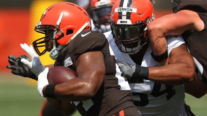 Cleveland Browns running back Nick Chubb, left, rushes past Cleveland Browns defensive end Olivier Vernon (54) during practice at the NFL team's training facility, Thursday, Aug. 27, 2020, in Berea, Ohio.