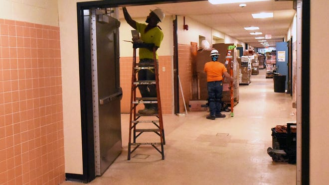 A crew member provides a finishing touch in one of the hallways of the new Sanford Middle School on Tuesday, Aug. 18, 2020. The district delayed the start of school for students in pre-K through eighth grade.