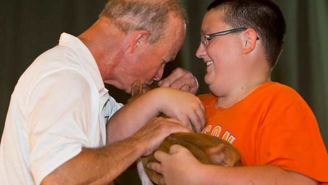 Purdue University President Mitch Daniels kisses a pig held by Hunter Dowell Thursday, July 24, 2014, during the Kiss-A-Pig contest at the Tippecanoe County 4-H Fair in Lafayette.