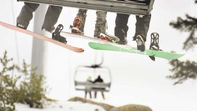 Snowboarders go up the Grandview Express chair lift at the Sierra-at-Tahoe ski resort in this photo from 2011.