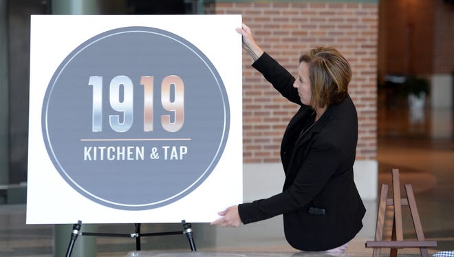 The logo of the new Lambeau Field Atrium restaurant, 1919 Kitchen & Tap, is unveiled by Jennifer Ark, the Green Bay Packers' director of stadium services, during a media conference at the Atrium on Tuesday, April 28, 2015.