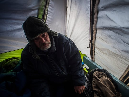 Don Abad talks to the free press from a tent site near