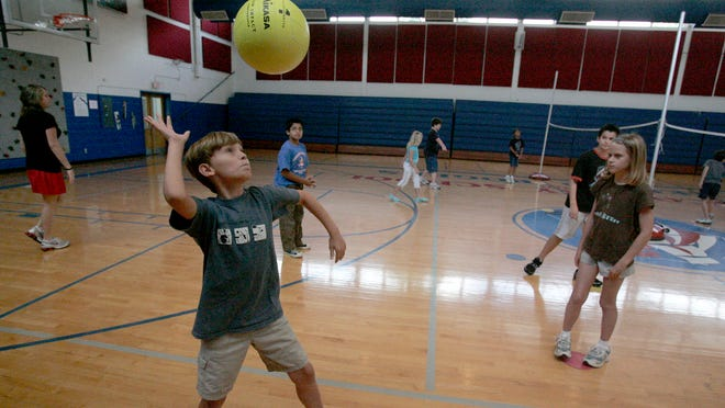 Ben Palmer serves the ball during a game of volleyball at The Discovery School at Reeves-Rogers play during gym class.