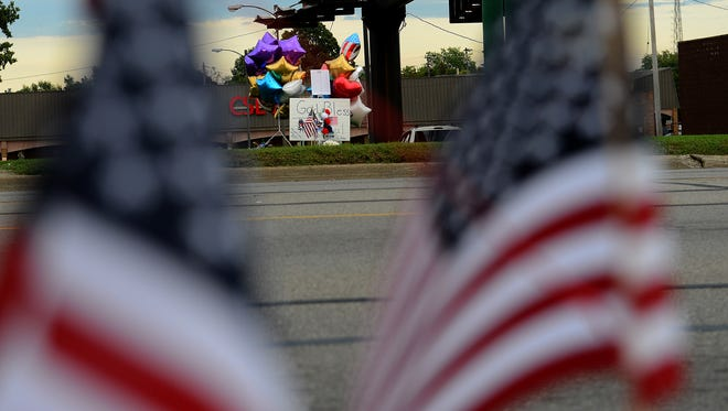 """Two roadside memorials sit on opposite sides of Cedar Street honoring fallen firefighter Dennis Rodeman Thursday night, September 10, 2015. Rodeman was killed after he was hit by a vehicle while collecting donatoins for the """"Fill the Boot"""" campaign on Wednesday."""