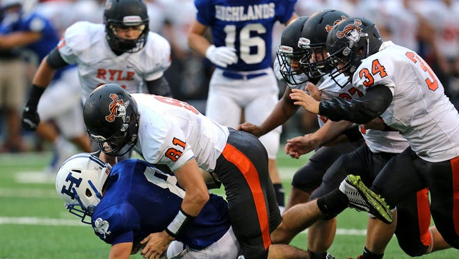Ryle DB Elijah Cusick tackles Highlands Nick Kendall for a loss in the first half of the game between the Ryle Raiders and the Highlands Bluebirds at Highlands High School.