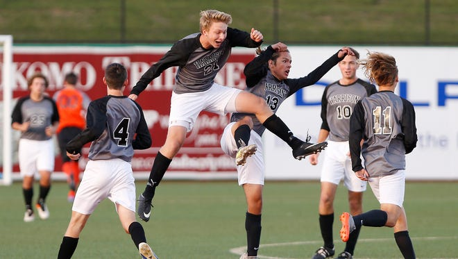 Harrison's Jerrick Mennen celebrates with Max Miller after his goal put the Raiders up 1-0 over Goshen in the first half of the soccer semistate Saturday, October 21, 2017, in Kokomo.
