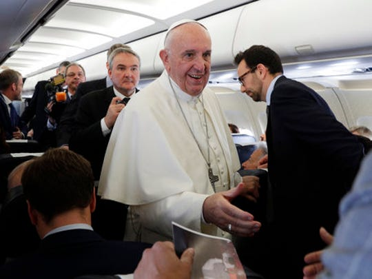 Pope Francis greets journalists on an airplane on his way to Egypt, Friday, April 28, 2017. Francis is in Egypt for a two-day trip aimed at presenting a united Christian-Muslim front that repudiates violence committed in God's name.
