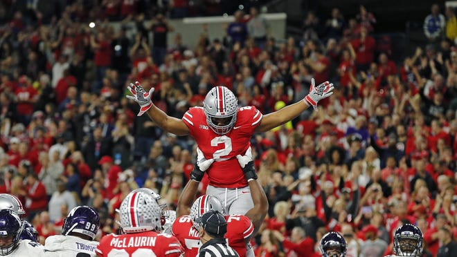 Ohio State Buckeyes offensive lineman Thayer Munford (75) throws up Ohio State Buckeyes running back J.K. Dobbins (2) into the air after he scored a touchdown against Northwestern Wildcats during the 1st quarter in the Big Ten Championship game in Indianapolis, Ind on December 1, 2018.