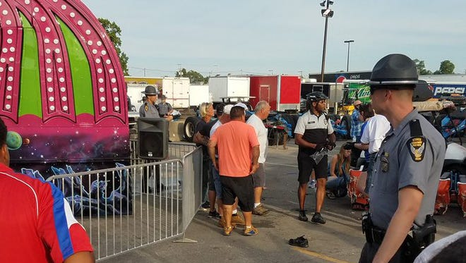 Authorities respond near the Fire Ball amusement ride after the ride malfunctioned injuring several at the Ohio State Fair, Wednesday, July 26, 2017, in Columbus, Ohio. Some of the victims were thrown from the ride when it malfunctioned Wednesday night, said Columbus Fire Battalion Chief Steve Martin. (Justin Eckard via AP)