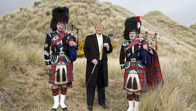 A fphoto taken on May 27, 2010, shows Donald Trump (center) posing with Scottish pipers during a visit to the construction site of his golf course on the Menie Estate near Aberdeen, Scotland.