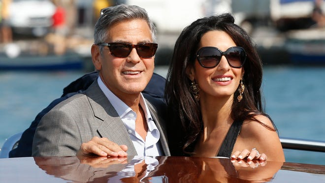 George Clooney, left, and Amal Alamuddin arrive in Venice, Italy, Friday, Sept. 26, 2014. Clooney, 53, and Alamuddin, 36, are expected to get married this weekend in Venice, one of the world's most romantic settings.