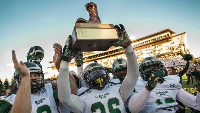 Quarterback Craig Leonard (8), safety Kevin Pierre-Louis (26) and other CSU players celebrate with the Bronze Boot last year after beating Wyoming in Laramie to earn the traveling trophy for the third straight year. Wyoming will try to win it back Oct. 1 at Hughes Stadium, in a game that will start at 8:15 p.m. and be televised nationally by ESPNU.