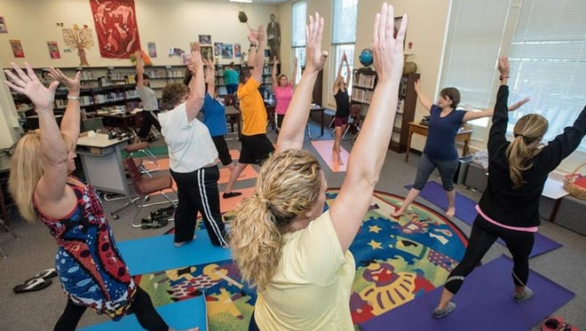 """Alexis Harris, PhD., right, an assistant professor from the University of Virginia Curry School of Education, faces Jefferson County Public School teachers gathered in the library at Bloom Elementary School as they stretch during a movement and experiential section of training in a Òcompassionate schools"""" pilot program between JCPS and the University of Virginia. June 11, 2015"""