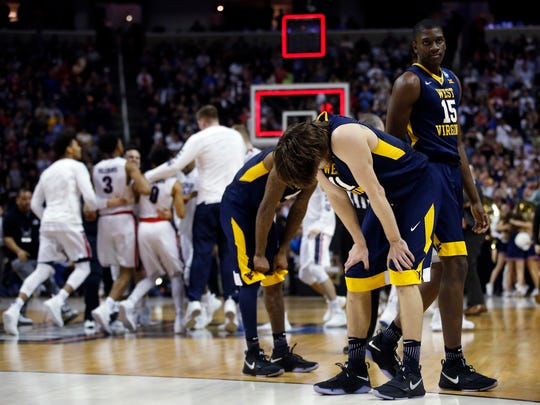 West Virginia players, foreground, react as Gonzaga celebrates a Sweet 16 win Thursday night in San Jose.