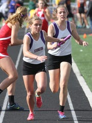 Lexington's Abby Miller takes the baton from Olivia Wolfe in the victorious 4 by 800 meter relay during the Ohio Cardinal Conference Championship at Wooster High School on Friday evening.