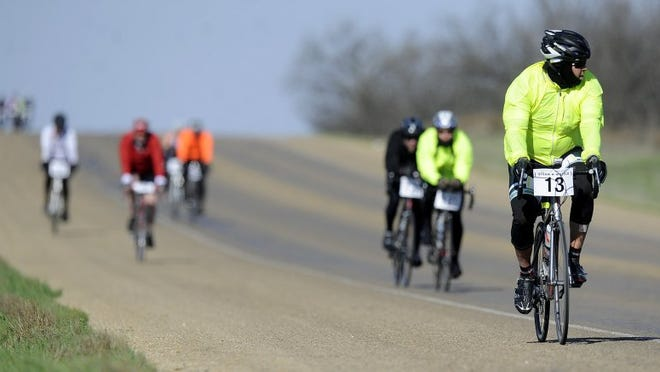 Thomas Metthe/Reporter-News Cyclists cruise down a hill on FM 18 during the Steam-N-Wheels bike race on Saturday, March 19, 2016.