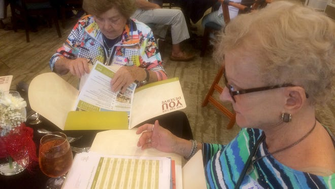 Rose Costaregni, 90, looks at marketing material from Sandalwood Village in Naples on Feb. 8, 2017.  Baiba Ausinsch, 73, is at right.