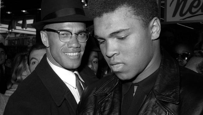 Muhammad Ali, right, is shown with Malcolm X, outside the Trans-Lux Newsreel Theater on Broadway at 49th Street in New York City on March 1, 1964.  They had just watched a screening of films on Ali's title fight with Sonny Liston earlier that year.