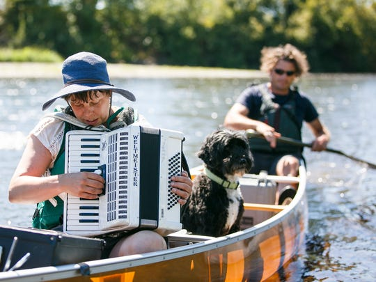 Jenny Conlee, an accordion player for Portland-based band The Decemberists, plays on the Willamette River as Travis Williams paddles their canoe on day two of Paddle Oregon on Tuesday, Aug. 16, 2016. Conlee joined the trip for the last twelve miles of Tuesday's scheduled 21-mile paddle, and played for the participants in Corvallis that night.