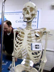 "Synthes mascot ""Fred Fibula"" shows off many of the orthopedic implants made by the Big Flats company during a manufacturing expo Friday."