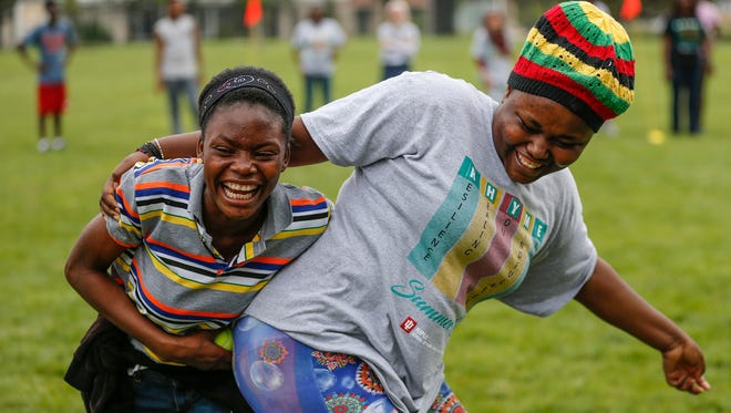 Yvette Iraguha, left, and Denise Muhoza try to carry a tennis ball with only their hips during the RHYME summer program for refugee high school students held on the IUPUI campus on Thursday, July 20, 2017.