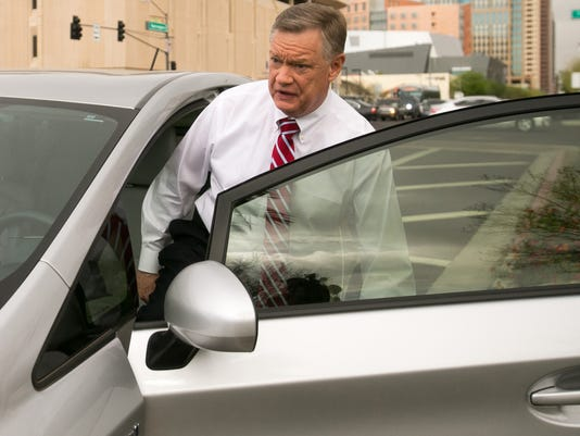 Former Fiesta Bowl executive director John Junker gets into his car outside the Sandra Day O'Connor U.S. courthouse after being sentenced in Phoenix on Thursday, March 13,  2014. Junker was sentenced to eight months in federal prison for participating in a scheme in which bowl employees made illegal campaign contributions to politicians and were reimbursed by the nonprofit bowl. (AP Photo/The Arizona Republic, Michael Schennum)  MARICOPA COUNTY OUT; MAGS OUT; NO SALES