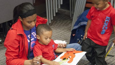 "Maria Waters reads to one of her twin sons, Laquan, while the other, Mario, looks on. The family came out for the 2014 ""Share A Story"" event at Jeffersonville (Ind.) Township Public Library."
