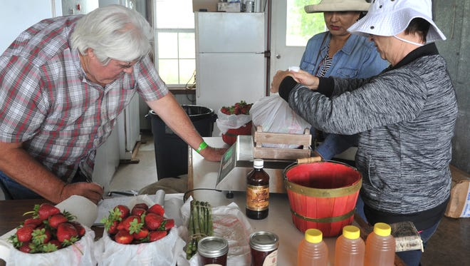 Clay County farmer Steve Young weighs the strawberries purchased by Belinda Hernandez and Natalia Gonzales, right, at the Young's Orchard and Berry Farm in Charlie.