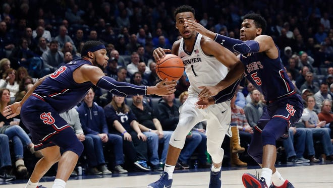 Xavier's Paul Scruggs (1) drives against St. John's Justin Simon (5) and Marvin Clark II, left, in the first half of an NCAA college basketball game, Wednesday, Jan. 17, 2018, in Cincinnati.