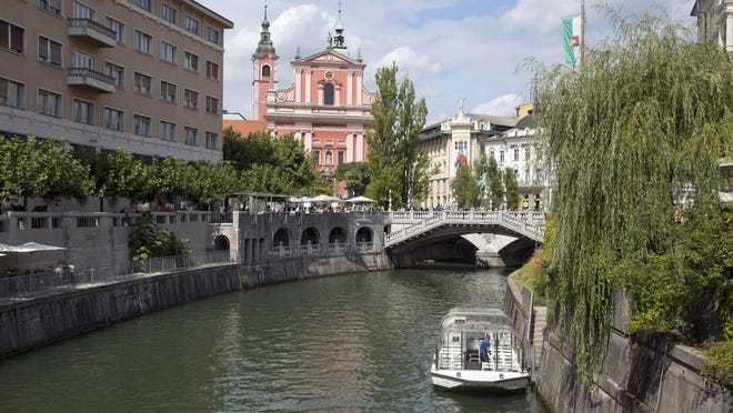 Tourists and residents in August walk across Tromostovje bridge in downtown Ljubljana, Slovenia. The tiny European nation is getting an outsize share of attention lately. Not only has Melania Trump, wife of U.S. President-elect Donald Trump, given her native country a boost of recognition, but Slovenia's also in the midst of a tourism boom.
