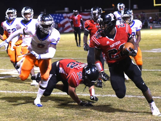 Parkway's Robert McKnight runs with the ball as he tries to get past Landry-Walker's defense in the 5A playoff football game Friday evening at Parkway's Preston Crownover.