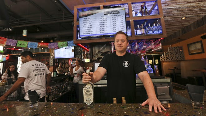 Frank Miller, a partner in a series of eight bars in San Diego, shows off some of the tequila collection at The Blind Burro, in San Diego, where the tequila prices can change every five minutes based on demand. The electronic Tequila Exchange board, behind and above Miller, shows the current prices for the bar's tequilas.