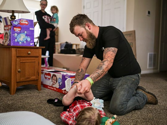 Josh Westeray, 27, changes Laney's diaper in the floor of his mother, Teresa Grider's, home. Westeray has five children that are currently in the custody of his mother, but he visits them often. April 27, 2017