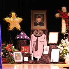 A collection of items is displayed Sept. 15, 2014, at the funeral service for Merrillville Police Officer Nick Schultz, who was shot last week when responding to a call,. Hundreds of officers, family and friends gathered at the Star Plaza Theatre for his service.