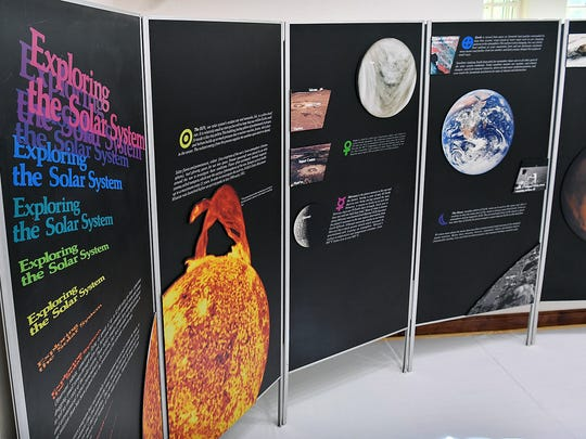 A large graphic wall provided by NASA explores a wide variety of space-related topics in the Youth ArtZeum Outer Space exhibit at the Kemp Center for the Arts.