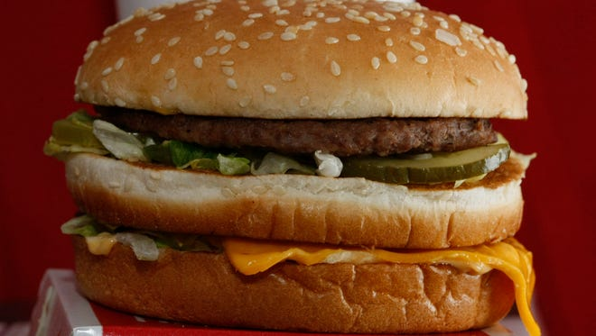 A Big Mac sandwich is displayed in front of a drink at McDonald's.