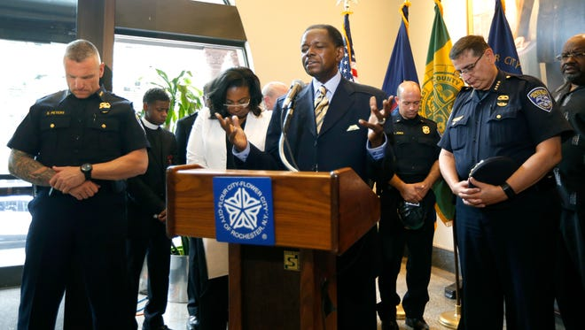 Pastor Roger Breedlove prays with Mayor Lovely Warren, Police Chief Michael Ciminelli, right, and others  during a ceremony at Rochester City Hall on Friday